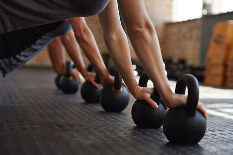 fitness class doing pushups on kettle bells
