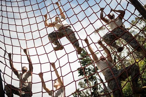 training team climbing rope wall