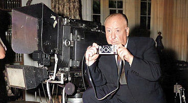 Alfred Hitchcock holding a Stereo Realis