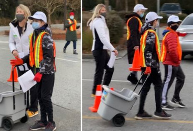 A family teams up to place cones in the parking lot.