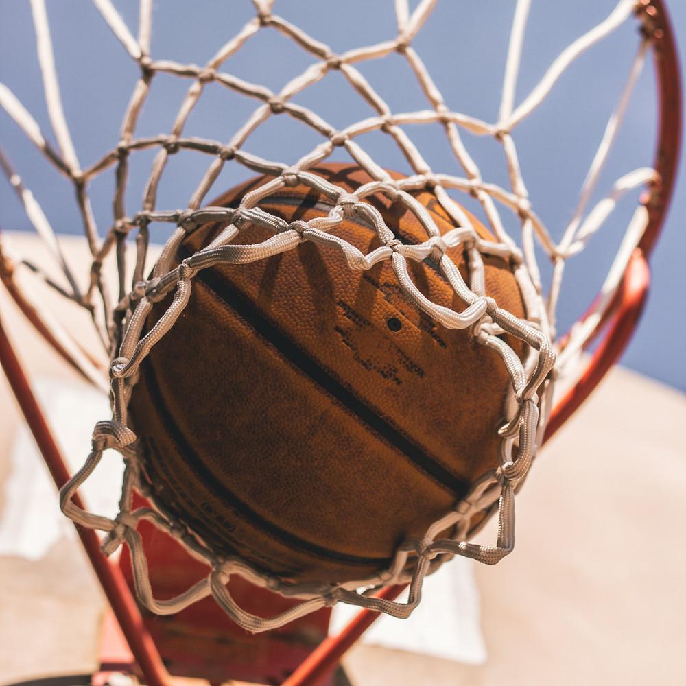 A basketball drops through the net.