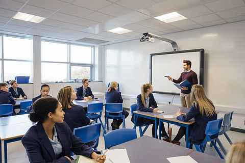 Male teacher is teaching a group of teenagers in a high school lesson.jpg