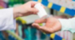 pharmacist hands passing pill bottle