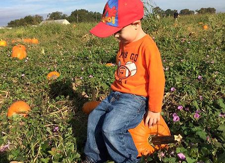 Little boy enjoying a rest on a pumpkin