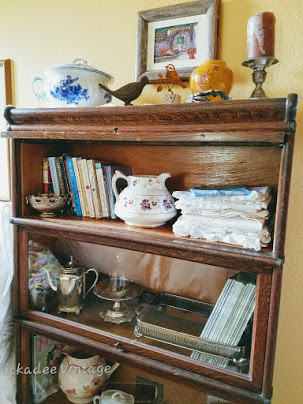 Stack of Antique White linens on Lawyer's bookcase