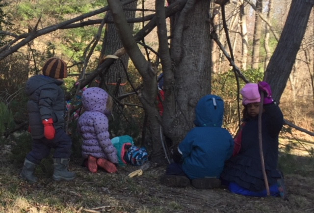 Children gathered by a fort built of sticks
