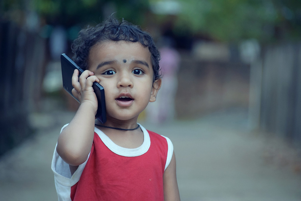 Little boy holding a cell phone to his ear