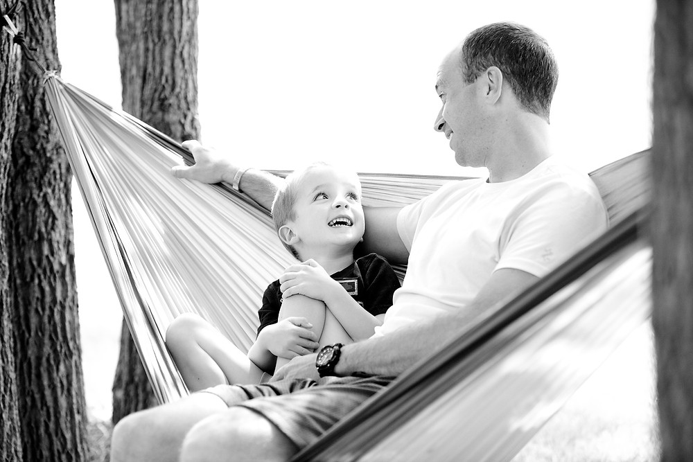 Father and son in a hammock, smiling and talking