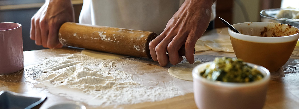 Hands holding a rolling pin on a table with empanada ingredients