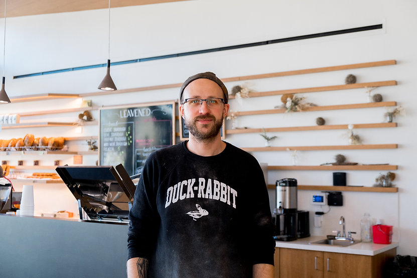 Ian Herrington, owner of Leavened Bakery in Cleveland, stands smiling in front of his bakery storefront