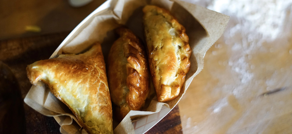 Three empanadas carried by a paper tray and napkin