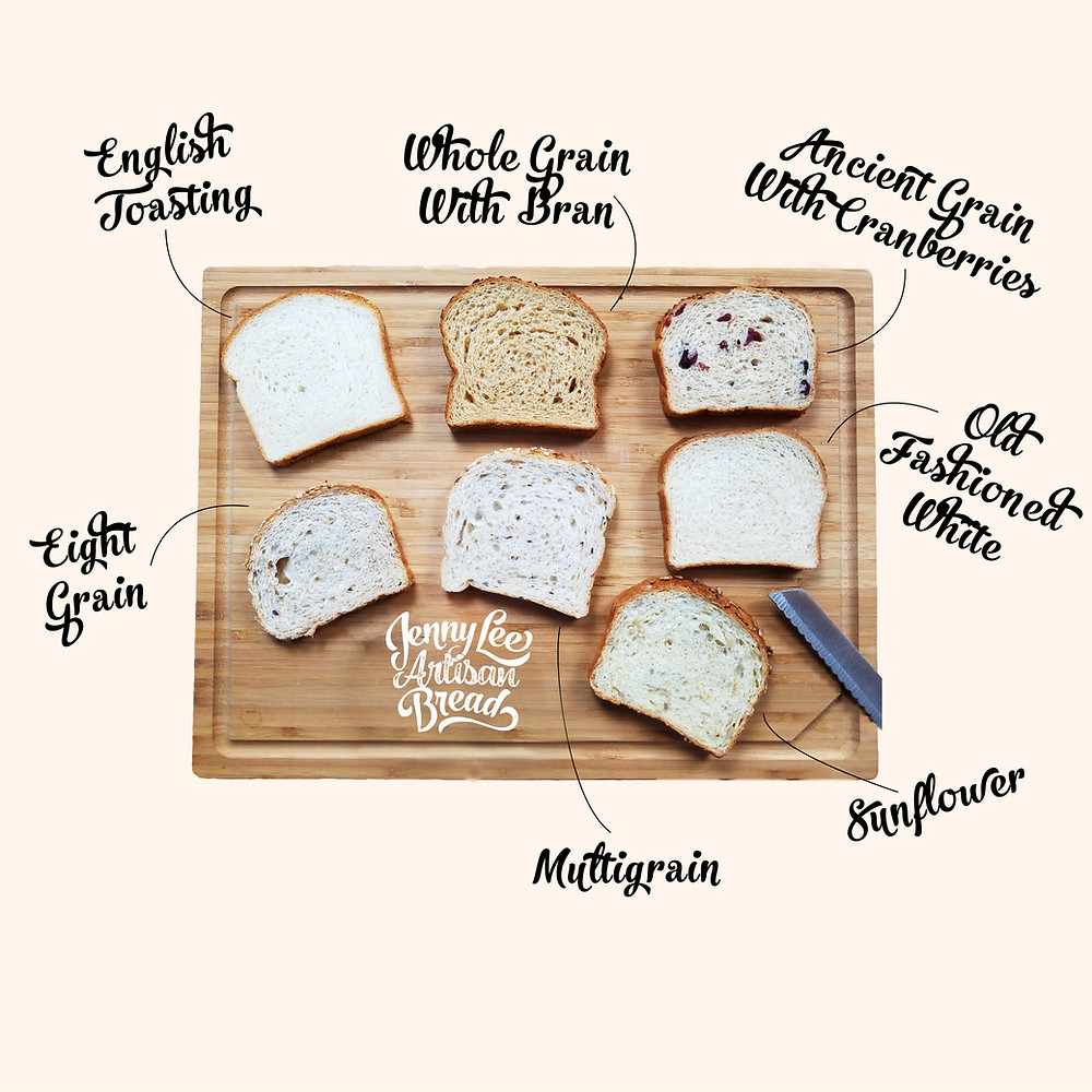An overhead shot of seven kinds of Jenny Lee Artisan Bread laid out on a wooden cutting board