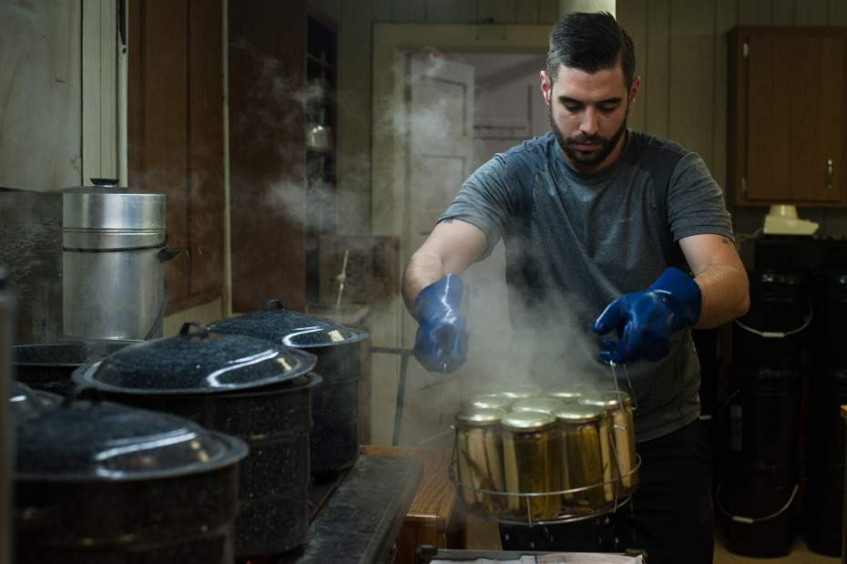 A man using food processing equipment at Pittsburgh Pickle Company in Verona
