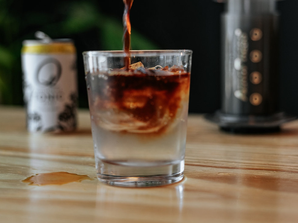 Americano iced coffee being poured into a cold glass
