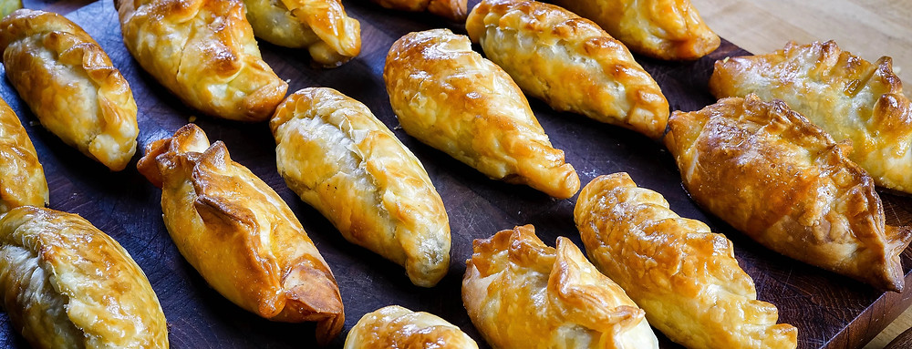 Several empanadas lined up and ready to be served