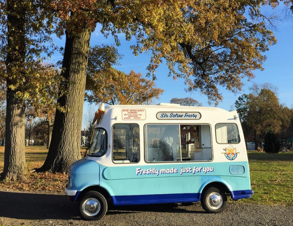 Millie's blue and white Ice Cream Truck in the outdoors next to trees