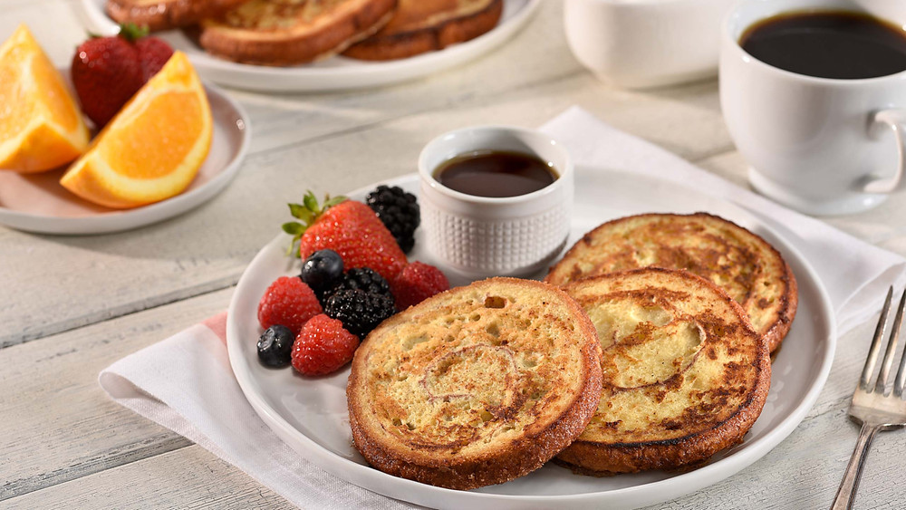 Plates of breakfast food including oranges, berries, french toast bread along with cups of syrup and coffee