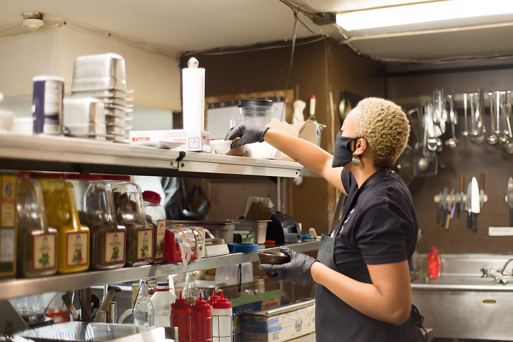 Keyla Nogueira Cook, owner of Casa Brasil, takes a dish from the shelf while working in the kitchen