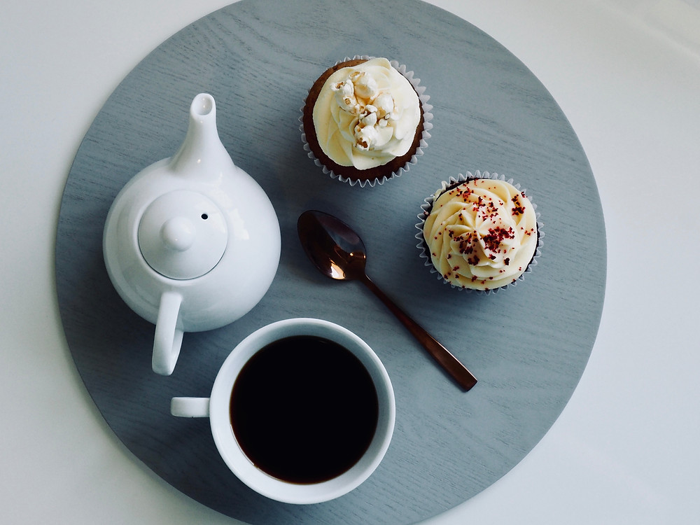 Overhead shot of a teapot, cup of tea, spoon, and cupcakes on a gray, wooden platter