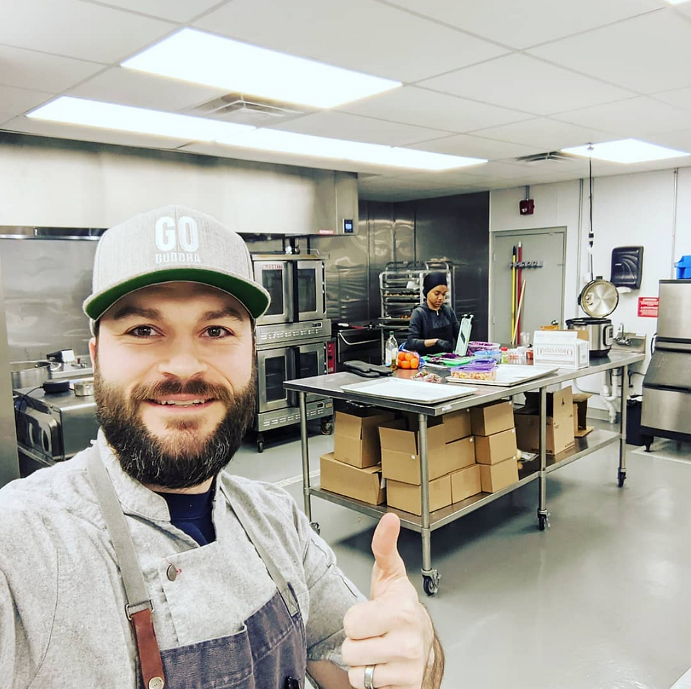 Josh gives a thumbs-up in front of his new commercial kitchen space