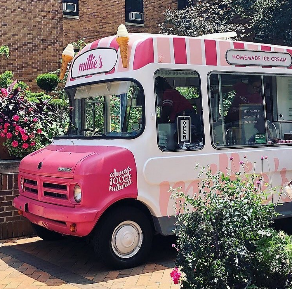 A pink and white Millie's Homemade Ice Cream Truck in front of a brick wall and flowers