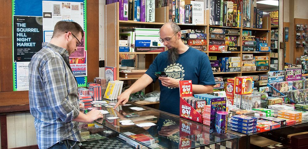Kylie, owner of Games Unlimited, helps a customer at the games counter