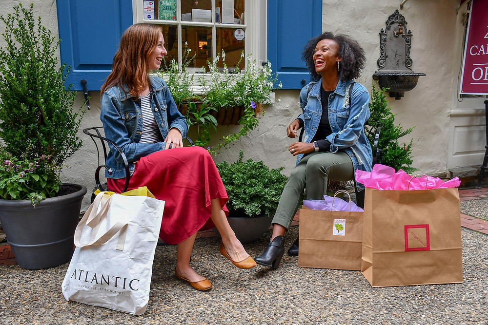 A pair of female shoppers sitting down with shopping bags outside a shop in Philadelphia