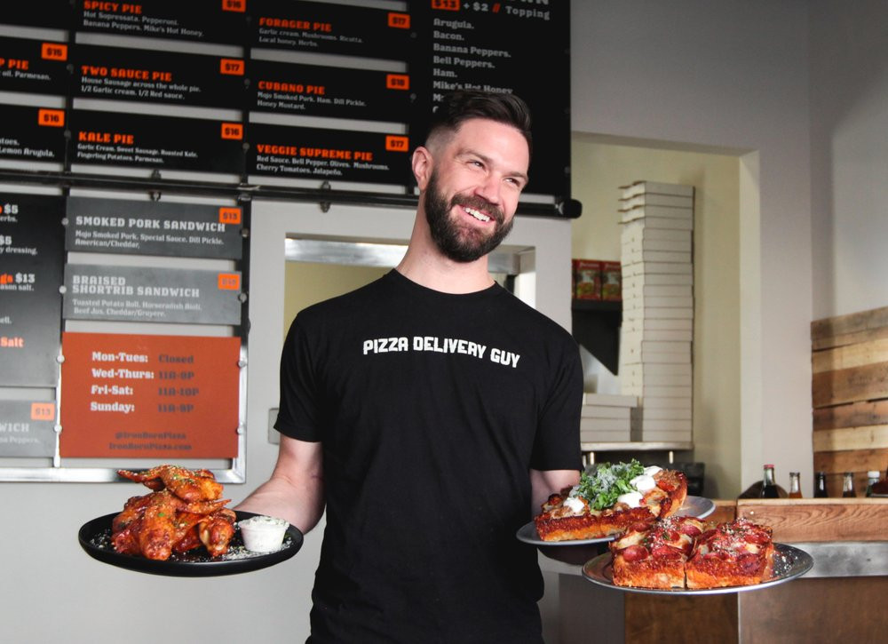 Pete Tolman, owner of Iron Born Pizza, poses smiling with two plates of pizza and a plate of wings