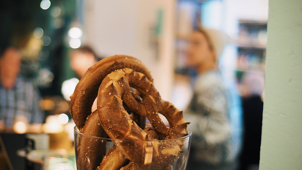 Multiple pretzels in a glass container in front of a bokeh background