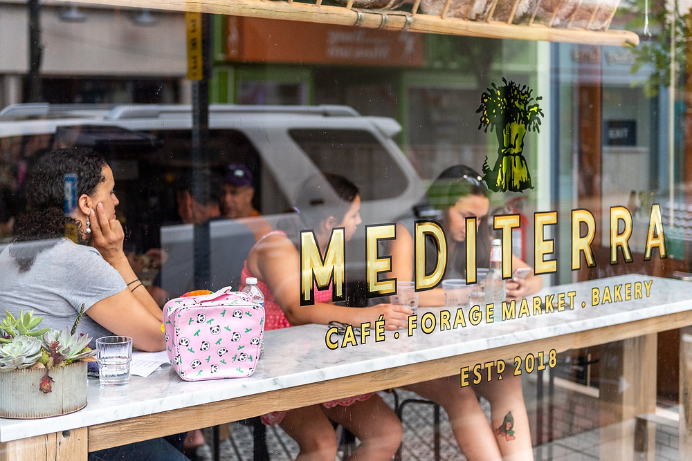 Customers at Mediterra Cafe in Sewickley, seen through the glass exterior window