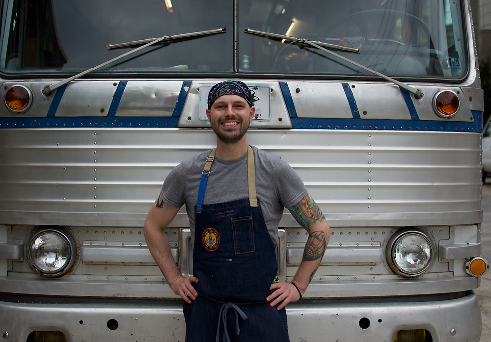 Luke Cypher, owner of Blue Sparrow Food Truck, in front of the bus funded by Honeycomb Credit