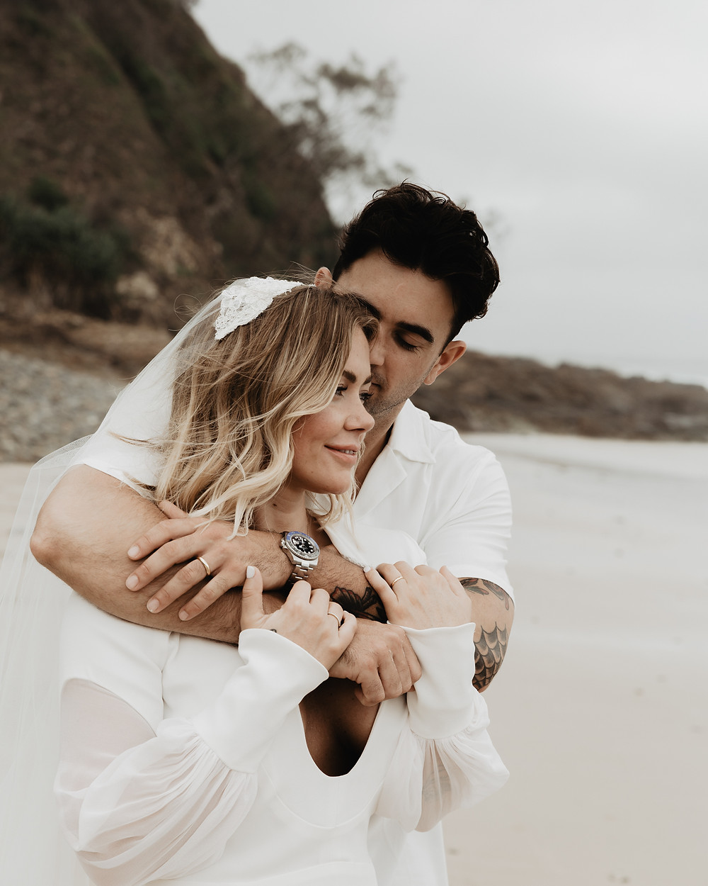 young married couple shares an intimate moment after eloping on the beach