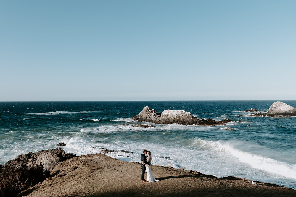 young married couple standing on the edge of Broken head cliff in Byron bay while waves crash behind them at sunset