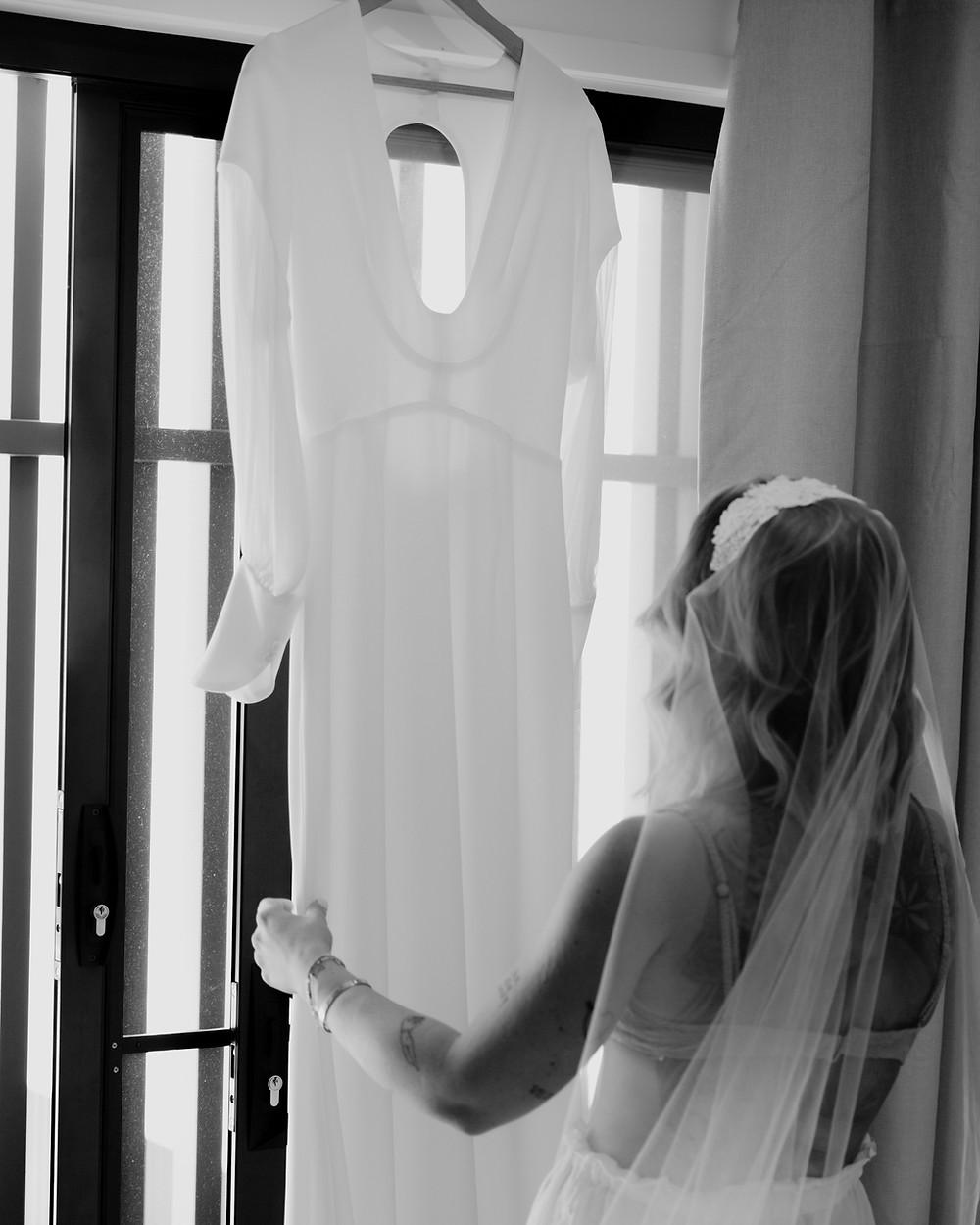 boho bride looks at beautiful wedding dress