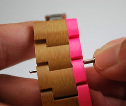 Pin protruding from wooden watch strap