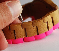 Pushing wooden watch strap pin back in