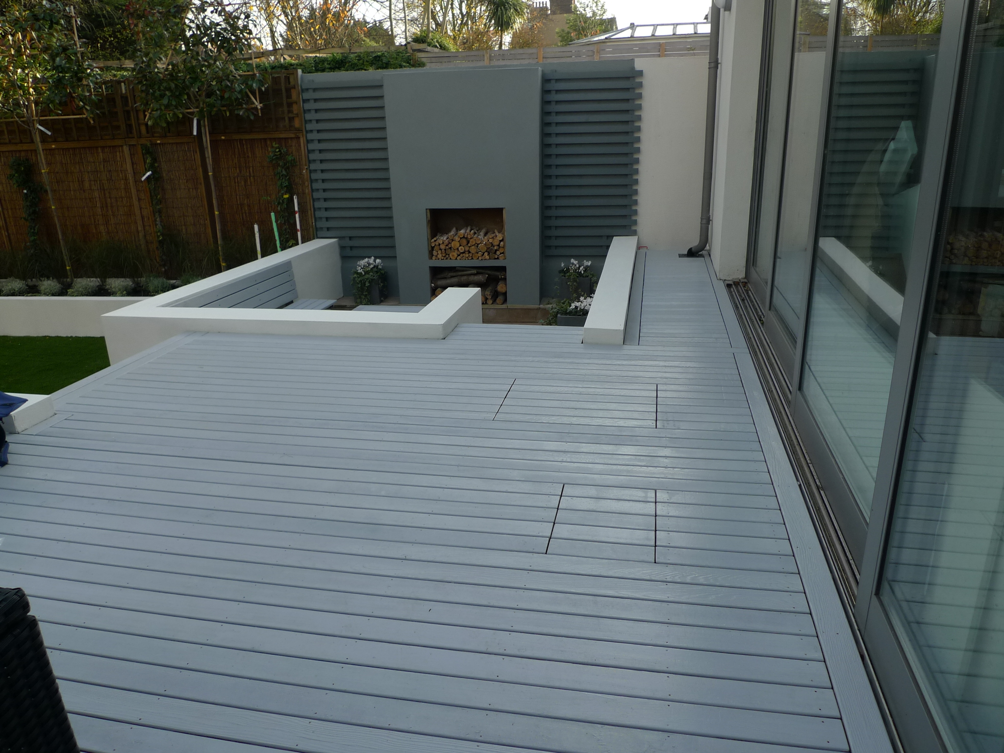 modern sleak garden low maintenance high impact garden design raised white wall beds grey decking ea