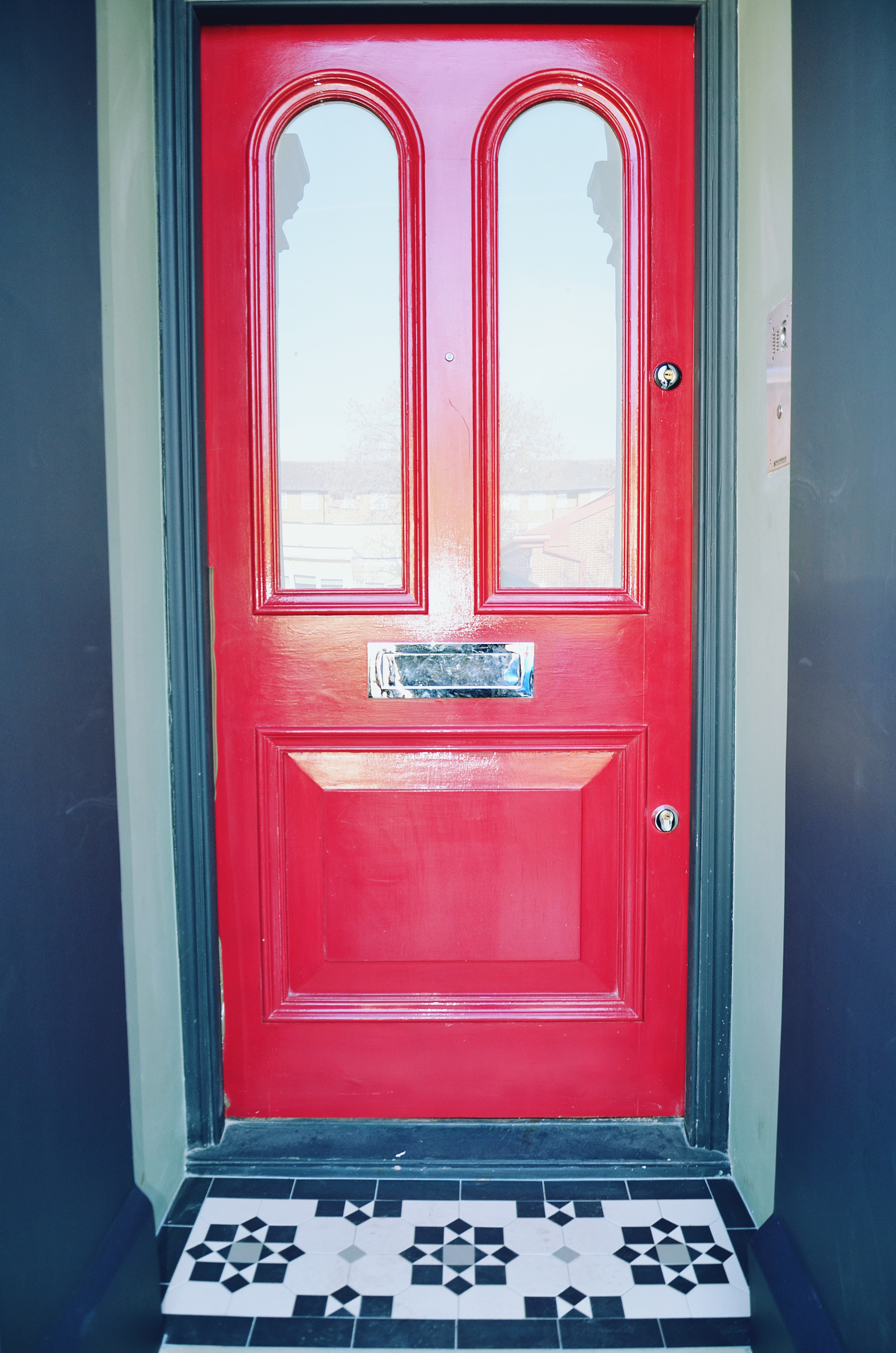 Victorian restoration with modern twist red door with porch mosaic