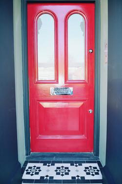 Victorian restoration with modern twist red door with porch mosaic