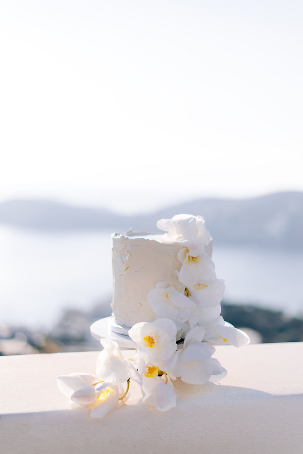 White wedding cake featuring The Isle's floristry