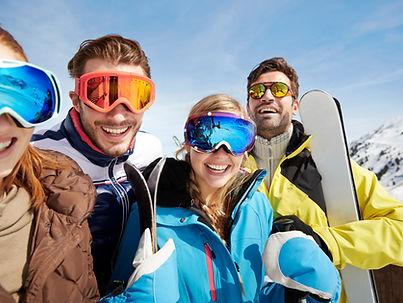Vänner bär skidor på bergstopp