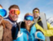 Amici che trasportano gli sci sulla cima