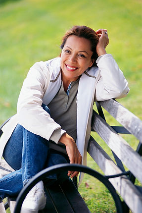 Image of bi-racial woman wth a smile sitting on a park bench, symbolizing fresh air as good for countering depression