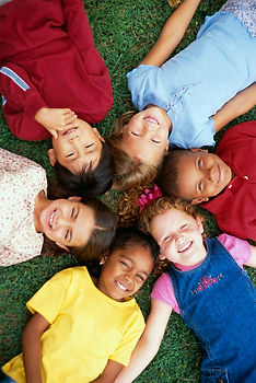 Image of 6 grade school kids lying on the grass with heads touching