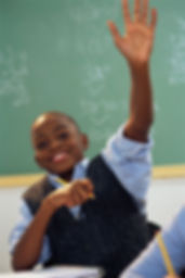 Image of a confident African American boy raising his hand in class