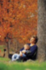 Image f a mother with a child in her lap, sittng in a park