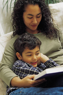 Image of a bi-racial mom reading to her son