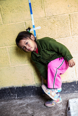 A girl putting her shoe back on after being measured and weighed as part of a nutrition program.