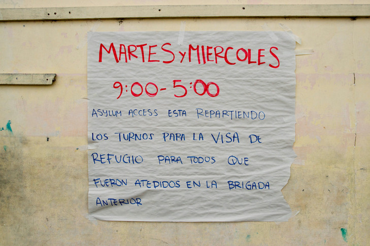 Sign inviting refugees to attend consult in the church in San Lorenzo.