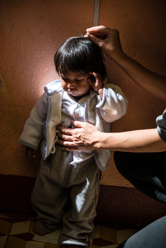 A girl being measured as part of a nutrition program targeting malnourished children.